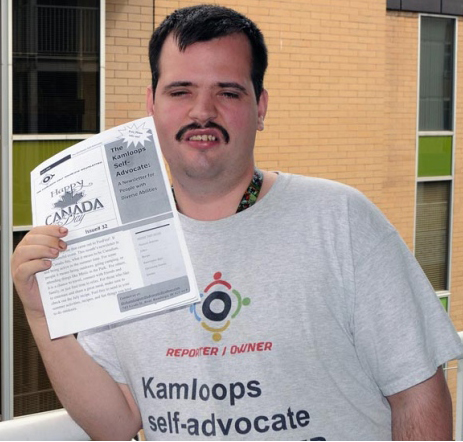 Picture of Krystian proudly showing a copy of his newsletter