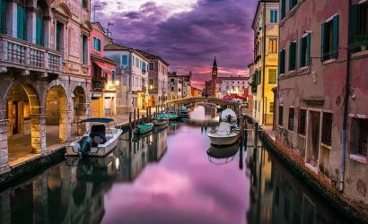 The canals of Venice sparkle brightly against dark evening clouds
