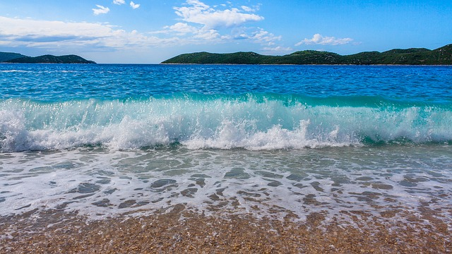 Gentle waves lapping at the beach beneath a bright blue sky