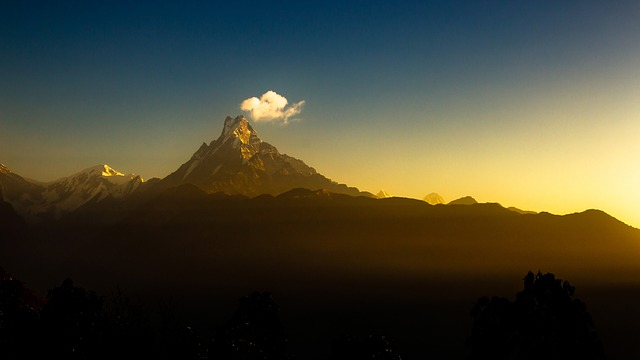 Fishtail or Machhapuchre mountain soars in the distance against a darkening sky and a s