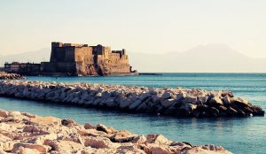 Picture an ancient castle set against a light blue sky as seen from the seawall