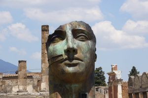 A large and calm face stans as a statue near Pompeii