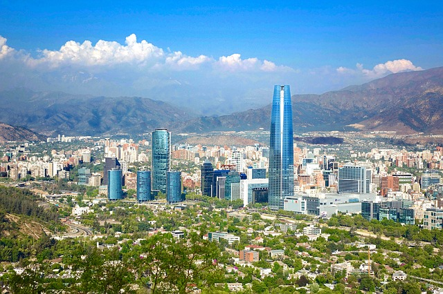 The skyline of Santiago Chile as seen from the sky; blue skies, mountains towering in the background, modern architecture mixed with old