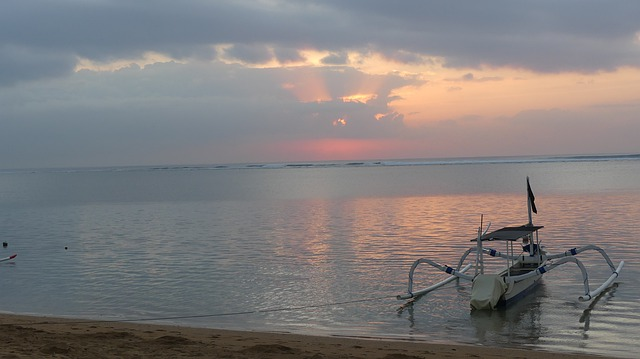 Beautiful picture of the sunrise glowing on the horizon from Sanur Beach Bali Indonesia