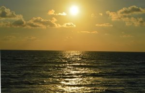 The sun sets in a golden glow over the Mediterranean Sea