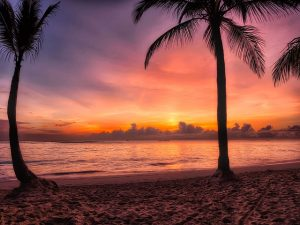 The sunrise glows a deep red orange as it rises over the Dominican Republic