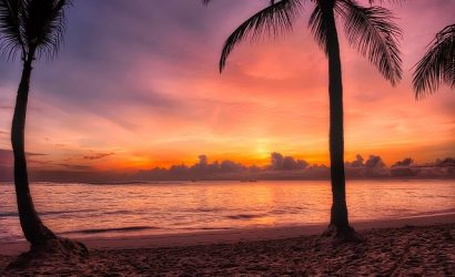 The sun shines orange and red as it rises over the Dominican Republic