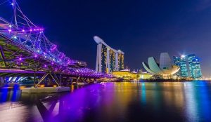 Singapore shines like a multicolored diamond against the deep blue of the evening sky